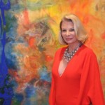 "Suzanne stands with her painting ""Seminal Dawn"" at the VIP Preview"